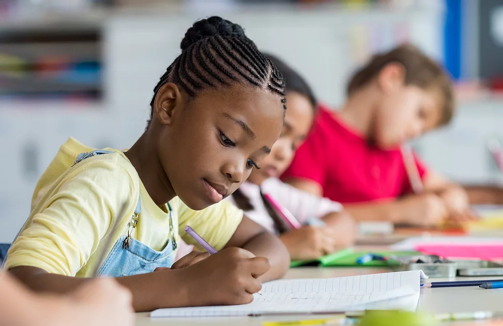 private tuition specialist pupil writing at desk in classroom